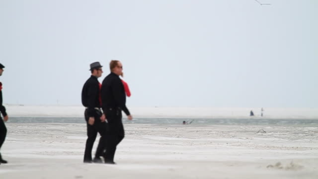 SLO MO WS Four men in black clothes and red ties walking across beach / Jacksonville, Florida, USA