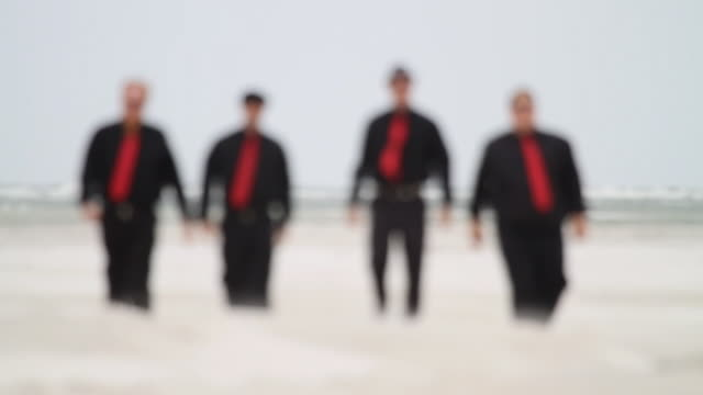 slo mo ws four men in black clothes and red ties walking across beach / jacksonville, florida, usa - schwarzes hemd stock-videos und b-roll-filmmaterial