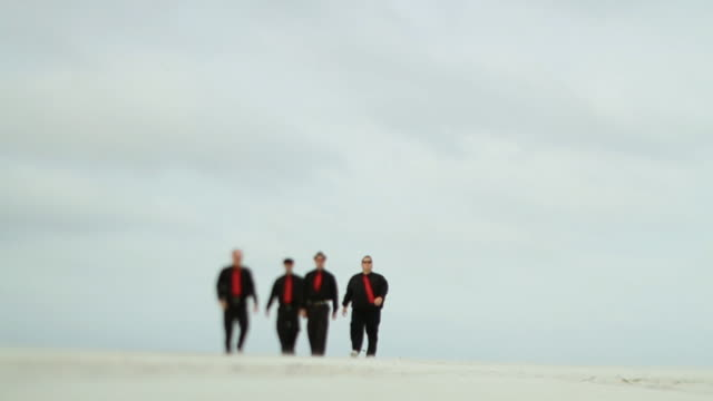 slo mo ws la four men in black clothes and red ties walking across beach / jacksonville, florida, usa - schwarzes hemd stock-videos und b-roll-filmmaterial