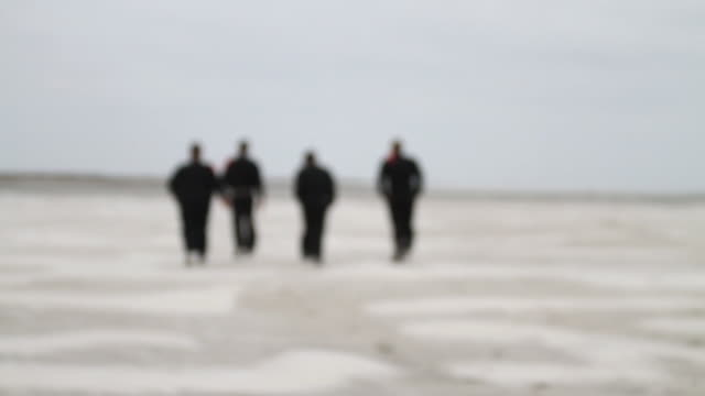 slo mo ws four men in black clothes walking across beach / jacksonville, florida, usa - schwarzes hemd stock-videos und b-roll-filmmaterial