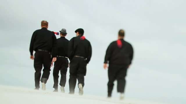 SLO MO WS LA Four men in black clothes walking across beach / Jacksonville, Florida, USA