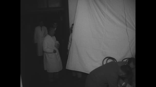 vidéos et rushes de vs four men in suits hunched over desk write on paper and look at it / group of doctors walking at night followed by nurses rolling sheetdraped... - autopsie