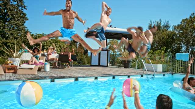 vídeos de stock e filmes b-roll de four men jumping into the pool together at a pool party while their friend cheer for them - festa