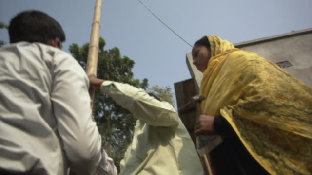 la, ms, tu, td, four men lifting up bamboo pole with attached solar panel into position in back yard, kaliakoir, bangladesh - bangladesh stock videos & royalty-free footage