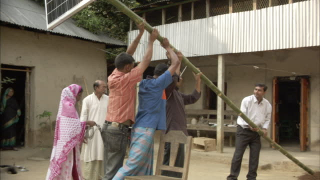MS, TU, ZI, Four men lifting up bamboo pole with solar panel into position in back yard, Mawna, Bangladesh