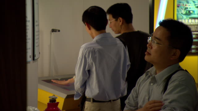 ms four men looking at exhibits in shanghai scientific energy conservation exhibition hall at shanghai energy resource center, shanghai, china - 展覧会点の映像素材/bロール