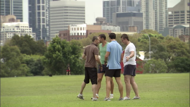 WS, Four men playing rugby in city park, Sydney, Australia