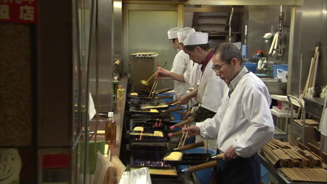 MS ZO Four men preparing omelets in restaurant kitchen Nishiki Market, Kyoto, Japan