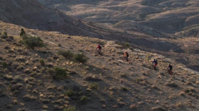 vídeos de stock, filmes e b-roll de quatro homens bicicletas de montanha de carona até uma colina de deserto - hobbie