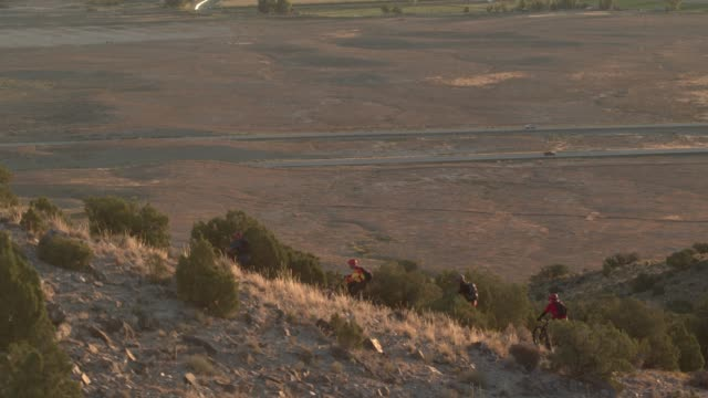 four men ride mountain bikes up a desert hill - trail ride stock videos and b-roll footage