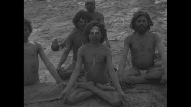 Four men sit in sand another reclines on blanket men are seminude younger boy walks through shot / Men wearing loincloths sit cross legged in sand...