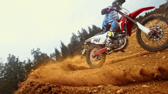 vier motocross-rennfahrer durch eine kurve - moving down stock-videos und b-roll-filmmaterial