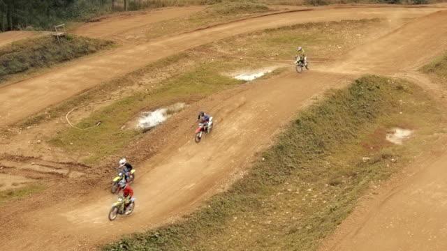 vidéos et rushes de aerial quatre coureurs de motocross racing - monter sur un moyen de transport