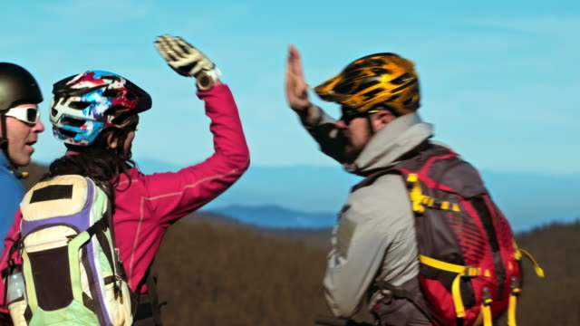 Four mountain bikers stopping and doing high five