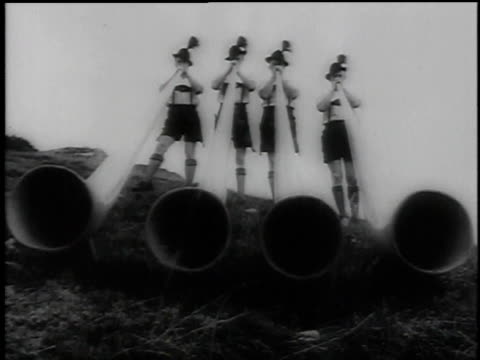1960 montage four mountaineers in traditional dress playing alp horns with narrator explaining history of the horn / germany - wind instrument stock videos & royalty-free footage