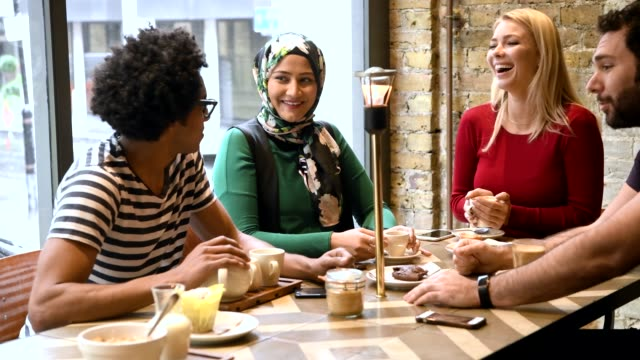 stockvideo's en b-roll-footage met vier multi raciale vrienden eten en praten in café - london england