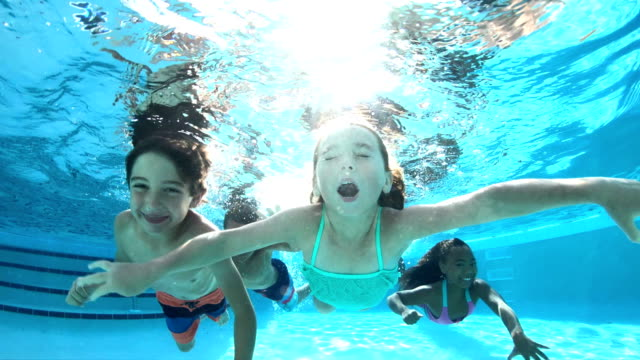 Four multi-ethnic children swimming underwater in pool