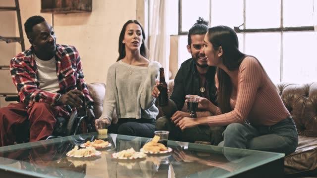 vídeos de stock, filmes e b-roll de quatro amigos multi-étnica, tendo alguns petiscos em casa no fim de semana - lanche