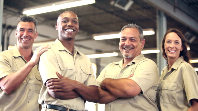 four multi-ethnic manual workers in warehouse - uniform stock videos & royalty-free footage