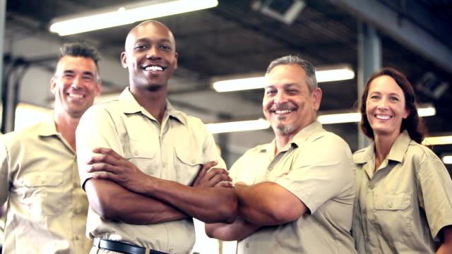 four multi-ethnic manual workers in warehouse - addetto alla manutenzione video stock e b–roll