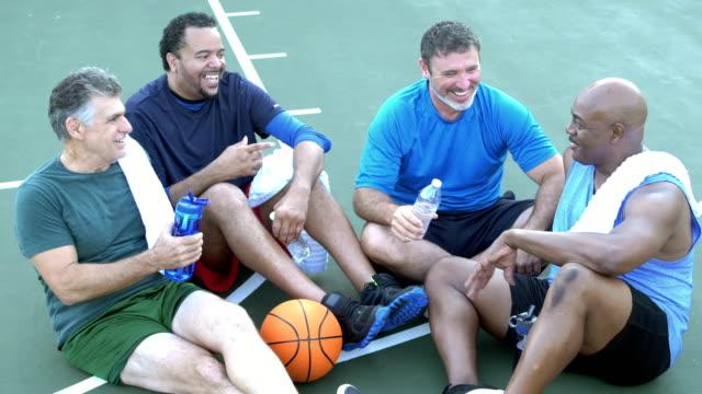 vidéos et rushes de quatre hommes multi-ethniques prenant une pause, jouant au basket-ball - 55 59 ans
