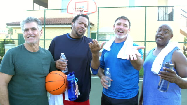 four multi-ethnic men taking a break, playing basketball - beckoning stock videos & royalty-free footage