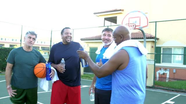 vidéos et rushes de quatre hommes multi-ethniques prenant une pause, jouant au basket-ball - centre culturel