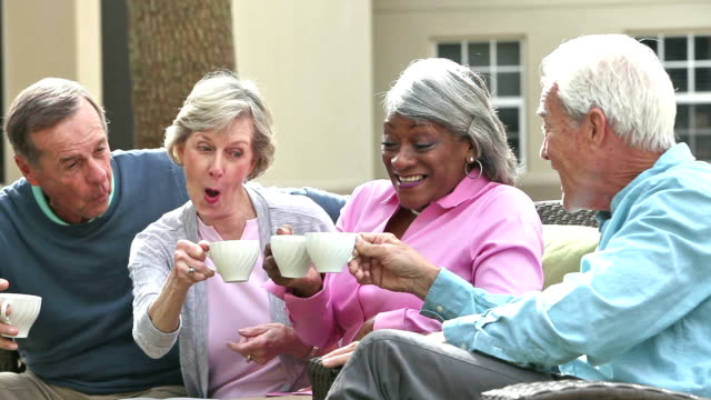 Four multi-ethnic seniors on patio, toasting coffee cups