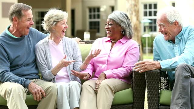 vídeos de stock, filmes e b-roll de quatro idosos multi-étnica sentado no pátio conversando - pátio