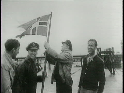 Four Norwegian men on small boat tethered to dock / American sailors come and shake hands with them / one man steadying Norwegian flag on boat other...