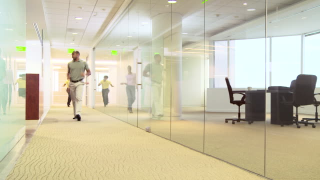 Four office colleagues dancing in hallway