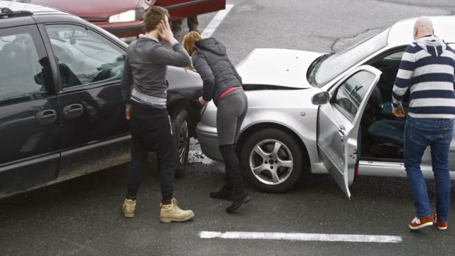 four people assessing the damage at the  scene of the car accident - incidente automobilistico video stock e b–roll