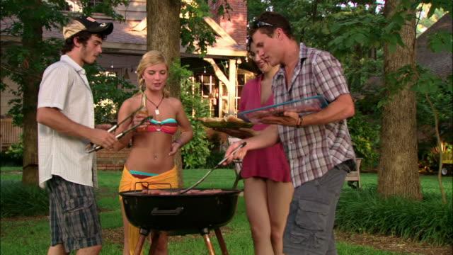 vídeos y material grabado en eventos de stock de ms four people having cookout on lawn/ texas - gorra de béisbol