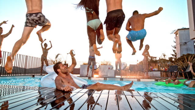 SLO MO Four people jumping into the water at a pool party at sunset and friends are taking photos and cheering for them