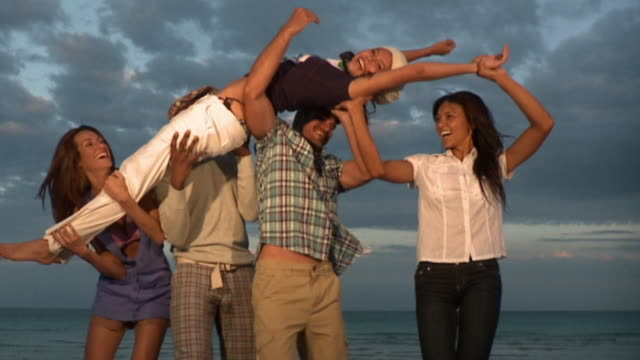 slo mo ms four people lifting up young woman on beach at dusk, south beach, florida, usa - five people stock videos and b-roll footage