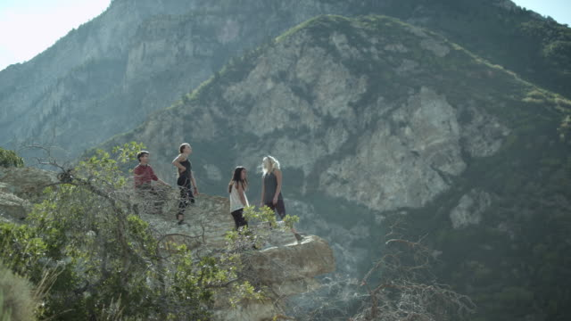 four people on a mountain rock outcropping. - belaying stock videos & royalty-free footage