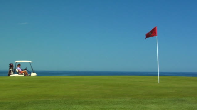 ws, four people passing in golf carts, flag on course in foreground, north truro, massachusetts, usa - 旗点の映像素材/bロール