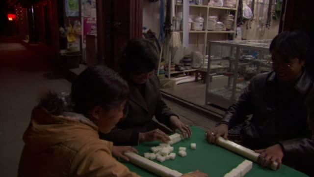 stockvideo's en b-roll-footage met ms cu four people playing mahjong on table outside of market stalls, weishan, yunnan, china - spelletjesavond