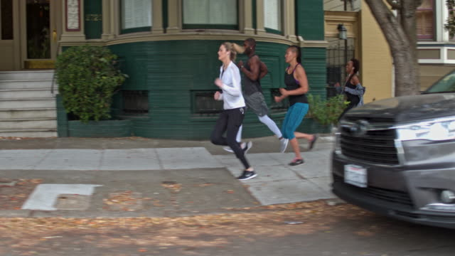 Four people running in the streets of San Francisco