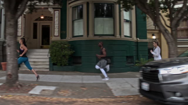 four people running in the streets of san francisco - piccolo gruppo di persone video stock e b–roll