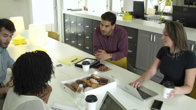 Four people talking in an office