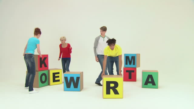 Four people using blocks to spell teamwork, time lapse