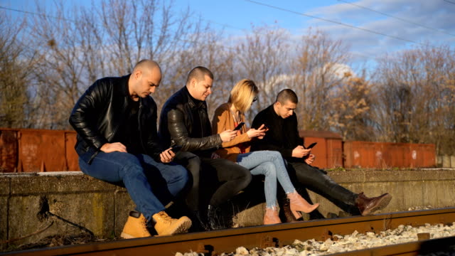 four people using phones on railroad station - leather jacket stock videos & royalty-free footage