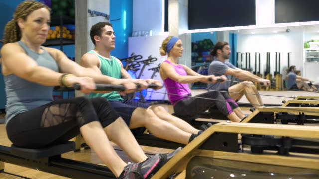 four people using rowing machines - rowing machine stock videos & royalty-free footage