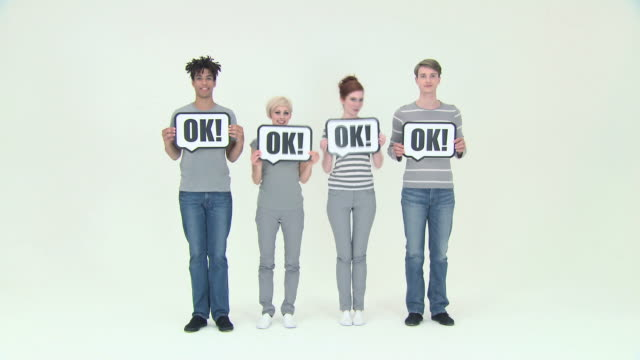 Four people with signs that say ok
