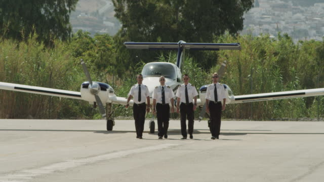 ls four pilots walking to camera in front of twin engine business aircraft, red r3d 4k - captain stock videos & royalty-free footage