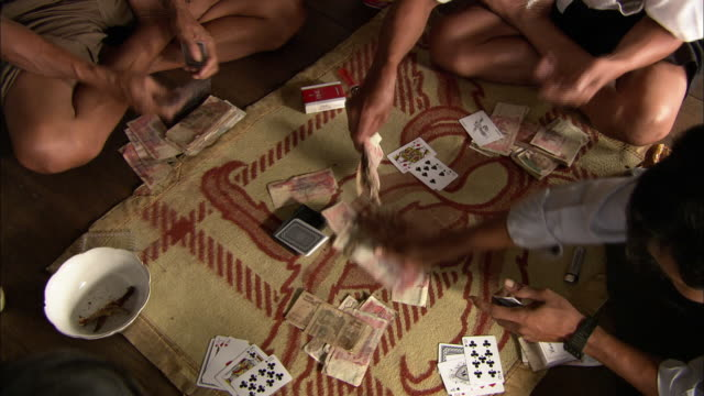 Four players sit on the floor around a rug and place bets as they play a card game.
