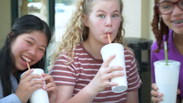 four playful tween girls with drinks, smiling for camera - 12 13 years stock videos & royalty-free footage