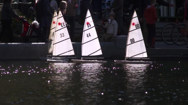 vidéos et rushes de four remote controlled sail boats sit still on central park pond - voile de bateau