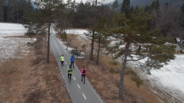 AERIAL Four runners running on a path on a cold day
